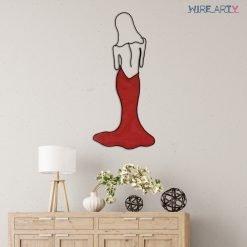 אישה בשמלה אדומה תלויה בקיר מעל מזנון