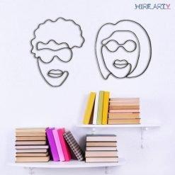 פסלים של גבר ואישה עם משקפיים תלויים על קיר