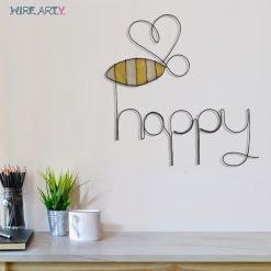 פסל של המילה happy עם דבורה תלוי על קיר